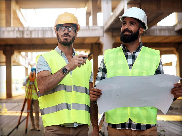 Dwóch mężczyzn trzymających plan budynku
